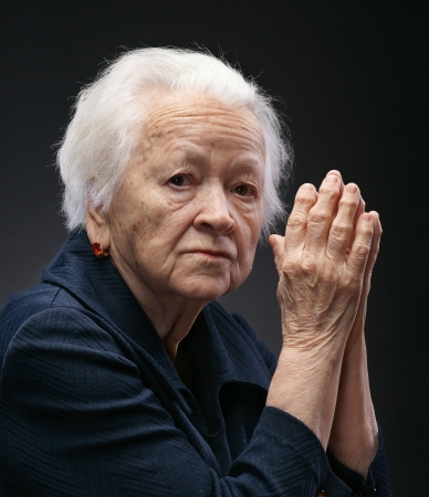 mature woman face: Portrait of old woman on a gray background