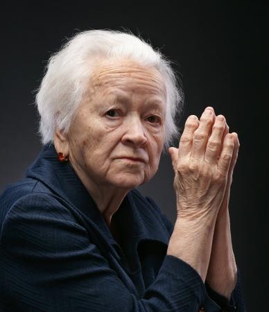 Portret van oude vrouw op een grijze achtergrond