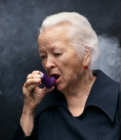 Senior woman with asthma inhaler on gray background