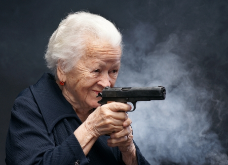 Old woman with pistol in smoke on a gray background