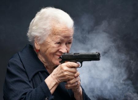 Oude vrouw met een pistool in rook op een grijze achtergrond Stockfoto