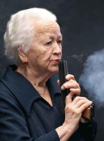 Old woman blows a smoke from a pistol on a gray background Stock Photo - 17062875