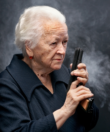Portrait of old woman with pistol in smoke on a dark background Stock Photo - 17062893