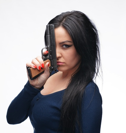 fashion shoot: Young girl with a pistol on a white background