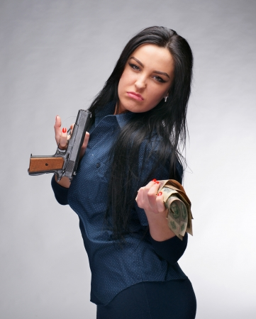 Young girl with pistol and old money on a gray background photo