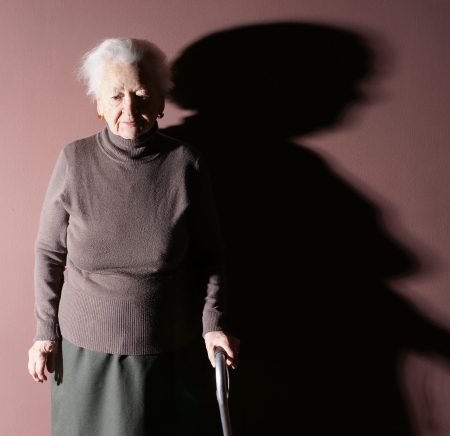 Old woman with a cane on brown background Standard-Bild