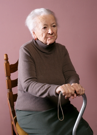 fine cane: Old woman sitting on a chair with a cane on brown background