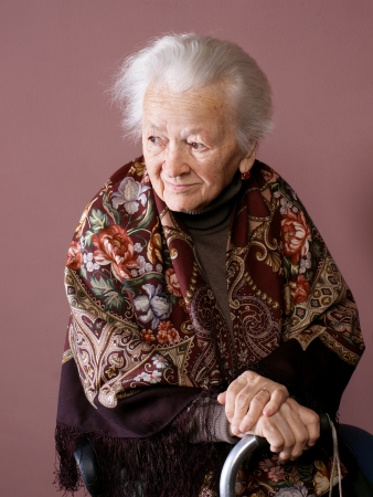 Oude vrouw met een stok op bruine achtergrond