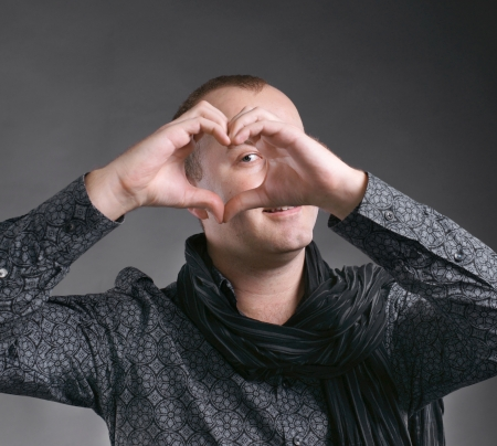 Young handsome man making heart sign on a gray background photo