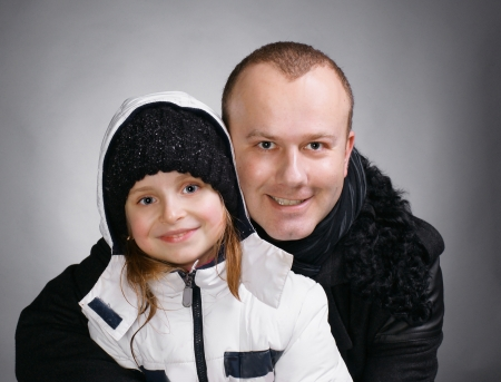 outwear: Smiling father and daughter in winter outwear on a gray background