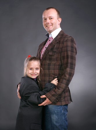 Smiling higging father and daughter both in suits  on a gray background Stock Photo - 17322051