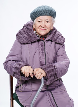outwear: Portrait of smiling old woman in winter outwear on white background