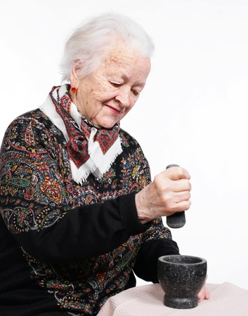 Old woman preparing the spices in a mortar on a white background photo