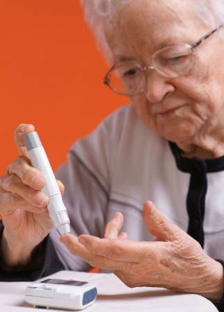 Old woman checking sugar level through glucometer on orange background