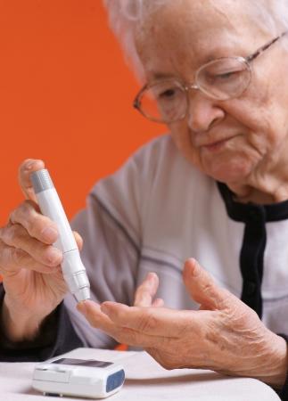 Oude vrouw de controle bloedsuikerspiegel door glucometer op oranje achtergrond
