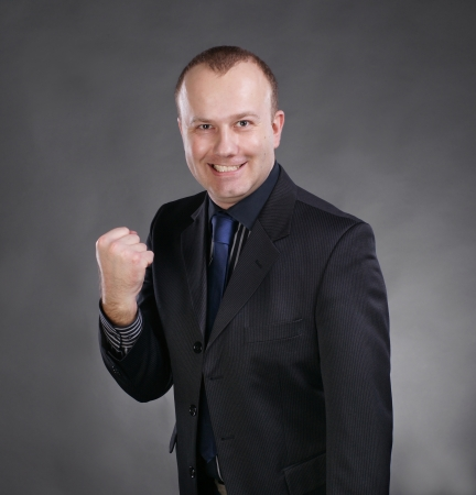 Excited young businessman celebrating victory on a gray background Stock Photo - 17503725