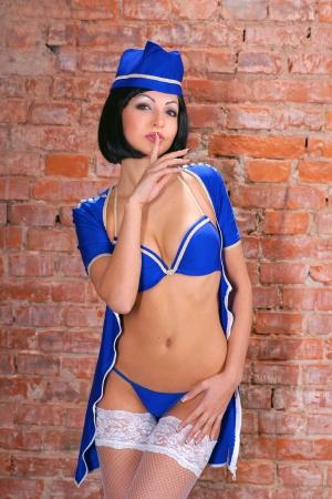 Sexy stewardess in blue uniform near the brick wall Stock Photo - 17506468