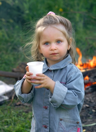 Pretty little girl drinking water outdoors            Stock Photo - 17565807