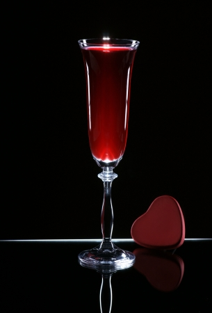 Glass of wine and heart on a dark background photo