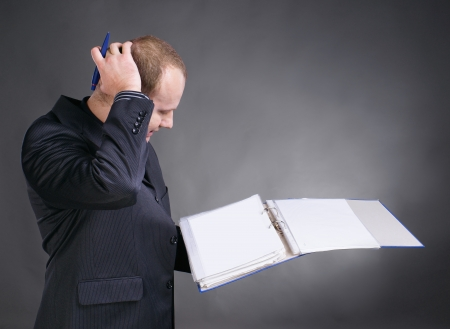 Young discouraged businessman checking documents in folders on a gray background
