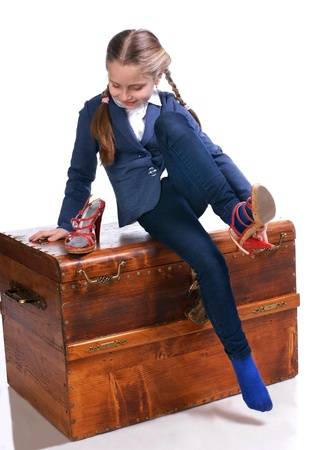 Beautiful girl sitting on a big box and trying on moms shoes Stock Photo - 17646428