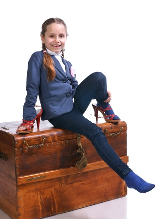 Beautiful girl sitting on a big box and trying on moms shoes  photo