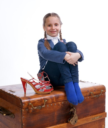 Pretty girl sitting on a box with moms shoes on a white background photo