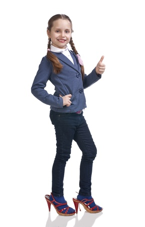 Pretty girl trying on moms shoes and showing yes sign on a white background Stock Photo - 17662142
