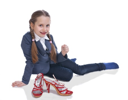 Pretty girl sitting on floor with moms shoes on a white background photo
