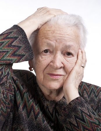 Portrait of old woman suffering from a headache on a white background photo