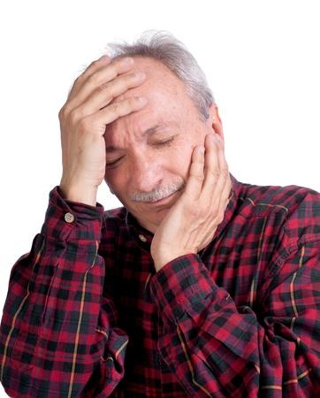 Senior man suffering from a headache on a white background 免版税图像