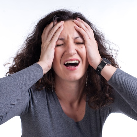 Young woman suffering from a terrible headache on a white background photo