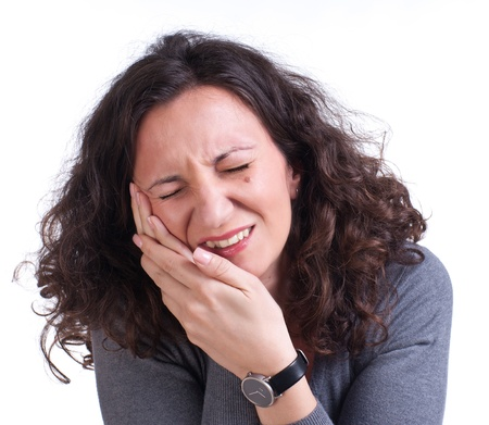 Young woman suffering from a toothache on a white background