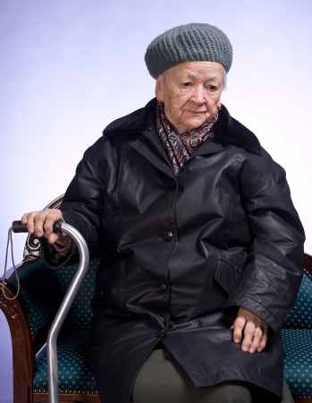 outwear: Old woman with a cane in winter outwear sitting on a chair Stock Photo