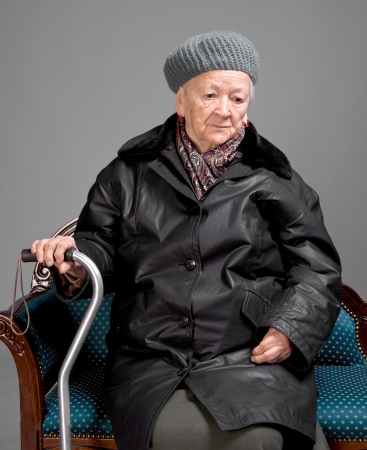 Old woman with a cane in winter outwear sitting on a chair photo
