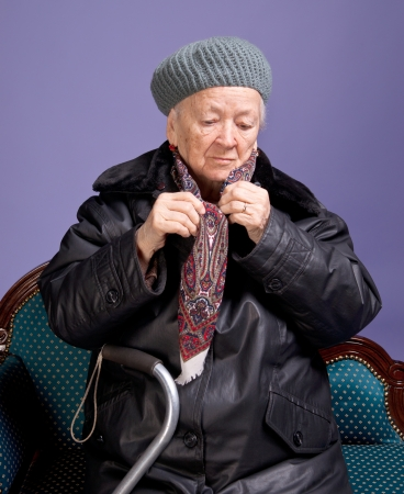 Old woman adjusting her scarf on a lilac background photo