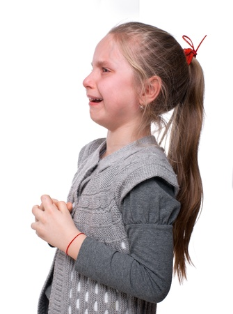 Little girl crying on a white background photo