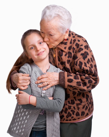 Grandmother kissing her granddaughter on a white background Stock Photo - 17897883