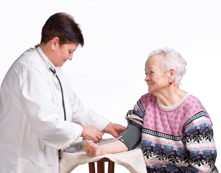 to pulsate: Elderly doctor and patient on a white background. Measuring pressure.