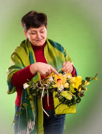 Beautiful senior woman with bouquet of flowers on a green background photo