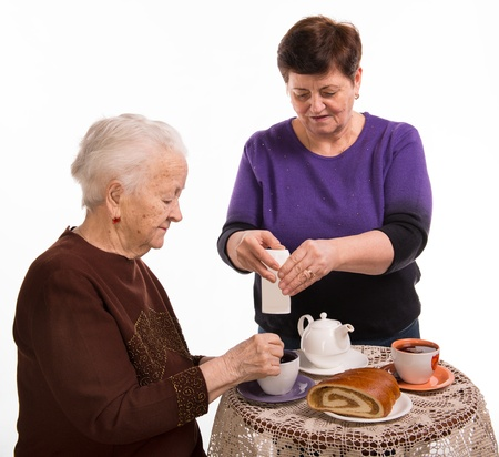 Mother having tea with her daughter on a white background Stock Photo - 18162757