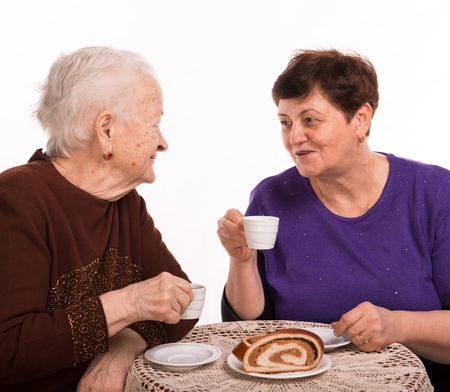 Mother having coffee with her daughter on a white background Stock Photo - 18162756