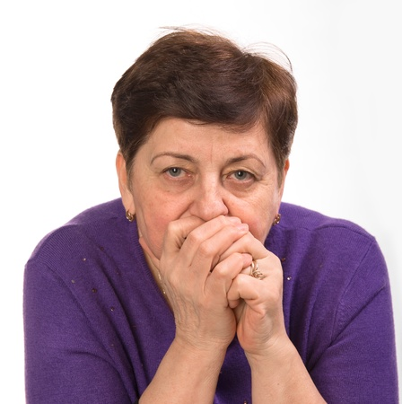 cautious: Close-up portrait of mature woman with hands on a mouth on a white background