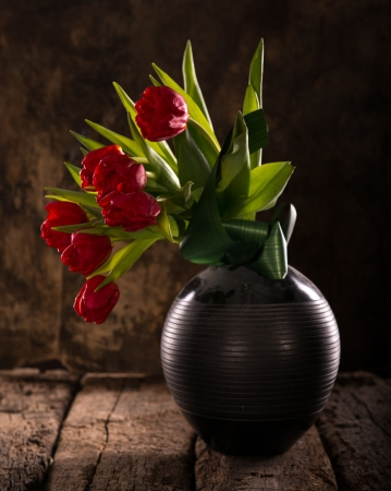 beautiful red tulips close up: Beautiful red tulips in black vase on a wooden background