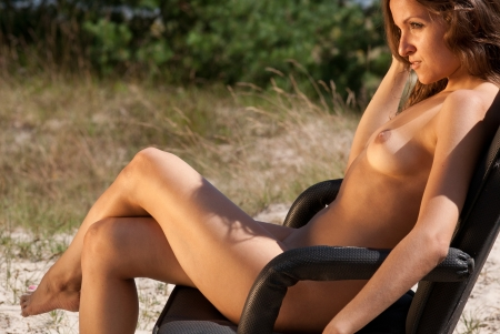 beach breast: Beautiful naked woman sitting on a chair on a nature background