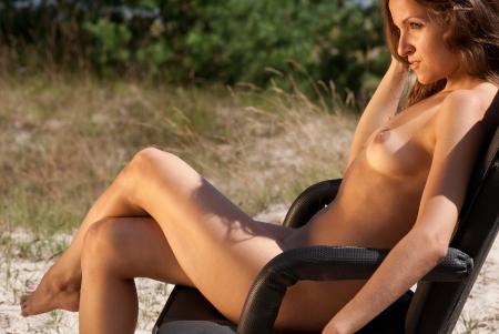mujer desnuda: Hermosa mujer desnuda sentada en una silla en un fondo de naturaleza