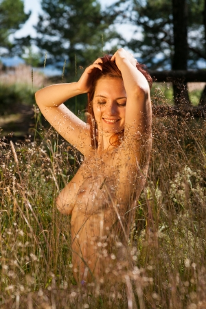 nude outdoors: Young woman in the grass on natural background in the sunlight