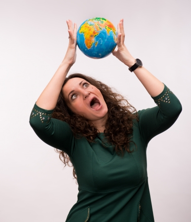Curly woman holding a globe on a gray background photo