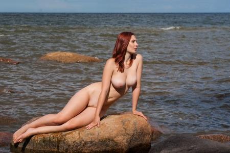 modelle nude: Giovane donna nuda seduta sulla pietra sullo sfondo del mare Archivio Fotografico
