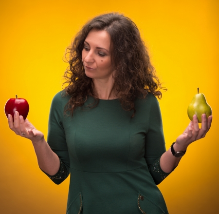 deliberation: beauty brunette with apple and pear on a yellow backgroung Stock Photo